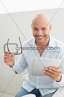 Casual smiling young man using digital tablet