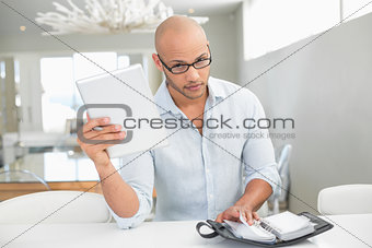 Casual serious man with digital tablet and diary at home