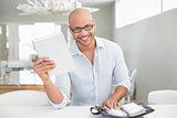 Casual smiling man with digital tablet and diary at home