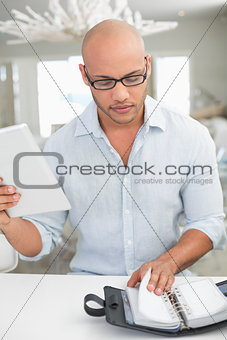 Casual man with digital tablet and diary at home