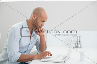 Concentrated casual man using laptop at home