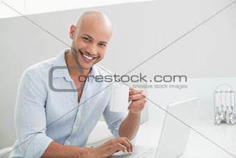 Casual man using laptop while drinking coffee at home
