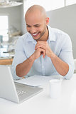Casual smiling man using laptop at home