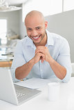 Smiling casual man using laptop at home