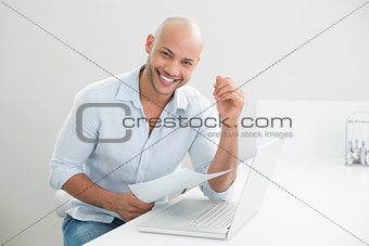 Portrait of smiling casual man with laptop at home