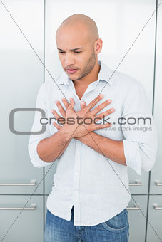 Casual young man with chest pain at home