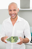 Smiling man holding a plate of broccoli