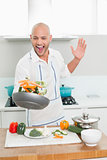 Cheerful man tossing vegetables in the kitchen