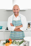 Smiling young man with vegetables in kitchen