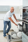 Smiling young man using dish washer in kitchen