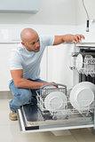 Serious man using dish washer in kitchen