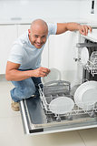 Portrait of a smiling man using dish washer in kitchen