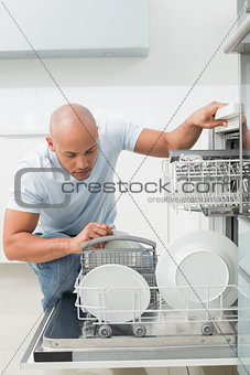 Serious man using dish washer in kitchen