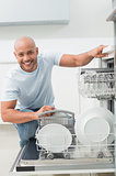 Portrait of smiling man using dish washer in kitchen