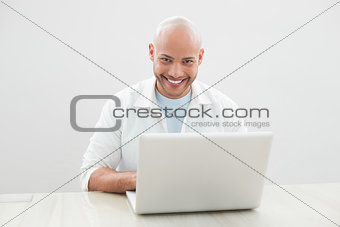 Portrait of casual smiling man using laptop at desk