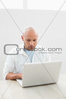 Casual serious young man using laptop at desk