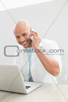 Casual smiling man using cellphone and laptop at desk
