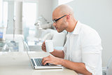 Concentrated casual man with coffee cup using laptop at home