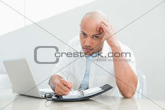 Casual serious man with laptop writing in diary