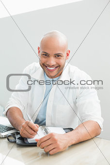 Casual smiling man with laptop writing in diary at home