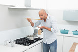 Man tasting food while preparing in kitchen