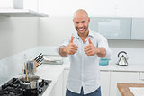 Smiling man gesturing thumbs up in kitchen