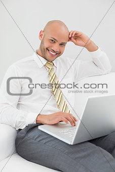 Smiling businessman using laptop on sofa at home