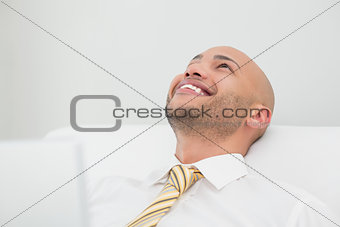 Close up of smiling elegant young businessman looking up