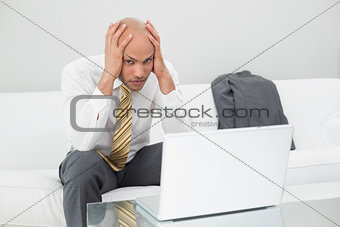Worried businessman with laptop holding head in hands at home