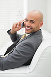 Smiling elegant businessman using cellphone on sofa at home