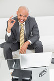 Businessman gesturing okay sign with laptop at home