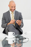 Smiling elegant businessman text messaging