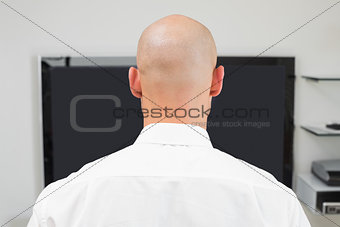 Close up rear view of a bald man using computer