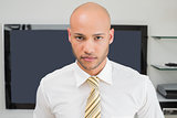 Portrait of a serious bald businessman at office