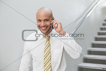 Smiling businessman using cellphone against staircase