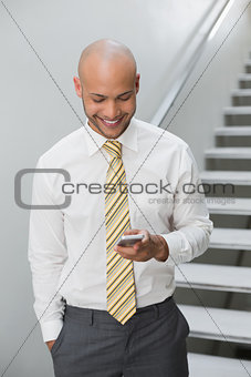 Smiling businessman text messaging against staircase