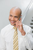 Smiling elegant young businessman using cellphone