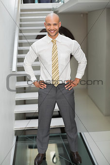 Smiling businessman standing against staircase