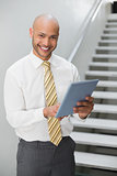Smiling elegant young businessman using digital tablet