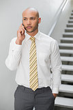 Serious elegant young businessman using cellphone