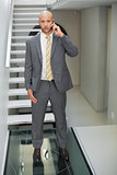 Elegant businessman using cellphone against staircase in office