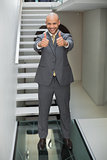Elegant businessman gesturing thumbs up against staircase