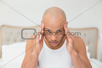 Close up of bald man suffering from headache in bed