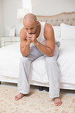 Thoughtful young bald man sitting on bed