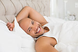 Portrait of smiling bald man resting in bed