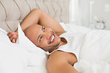 Smiling young bald man resting in bed