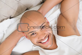Close up of a smiling young bald man resting in bed