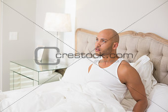 Thoughtful young bald man sitting in bed