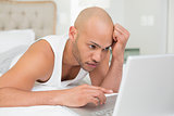 Serious casual bald young man using laptop in bed
