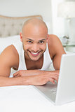 Smiling casual bald man using laptop in bed